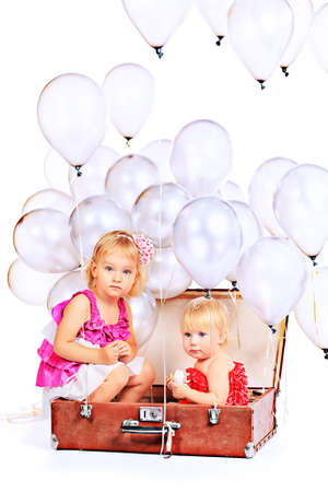 Two little girls are sitting in the old suitcase under many balloons. Isolated over white. Stock Photo - 15608457