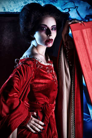 bloodthirsty: Bloodthirsty female vampire standing near the coffin on the night cemetery. Stock Photo