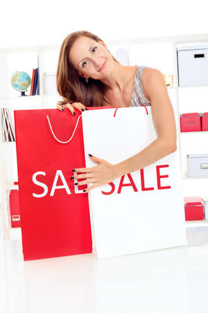 Seasonal sale: happy young woman holding shopping bags inside of a store. photo