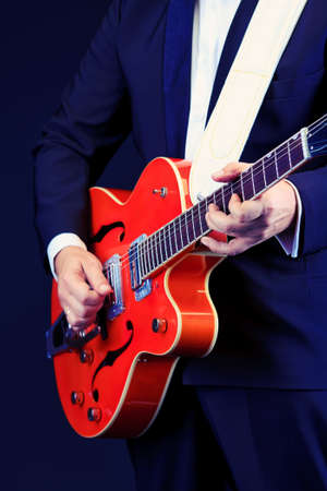 Close-up of a professional artist playing on guitar. Over black background. Stock Photo - 15684256