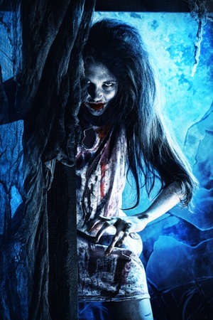 Bloodthirsty zombi standing at the night cemetery in the mist and moonlight. photo
