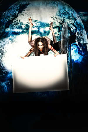 bloodthirsty: Female zombi flying at the night cemetery in the mist and moonlight and holding white board.