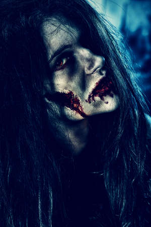 devil woman: Bloodthirsty zombi standing at the night cemetery in the mist and moonlight.
