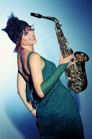 Professional musician posing with her saxophone at studio. Stock Photo - 15684273
