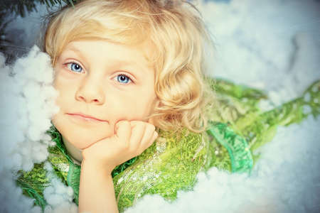 Happy little girl in Christmas dress lying in snow. photo