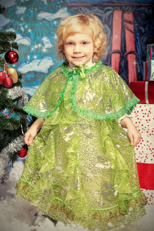 Happy little girl posing in Christmas dress. photo