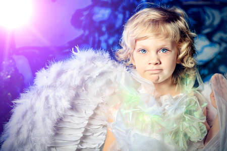 Beautiful little angel girl over Christmas background. photo