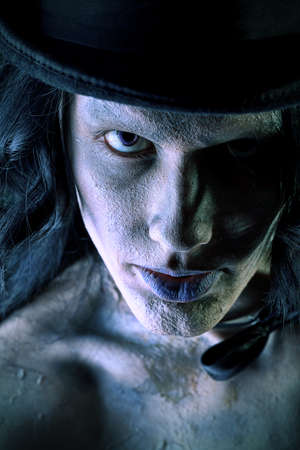 bony: Close-up portrait of a gloomy vampire standing at the night background. Halloween. Stock Photo