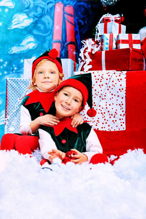 Two cute children in christmas elf costumes posing over christmas background. photo