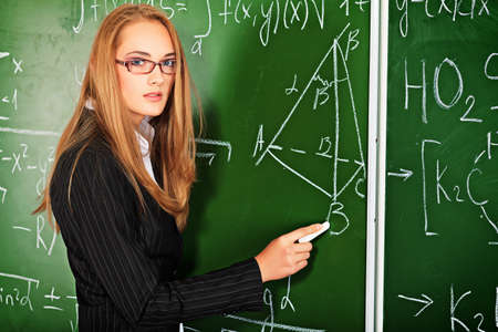 purposeful: Pretty student girl standing at the blackboard in the classroom.
