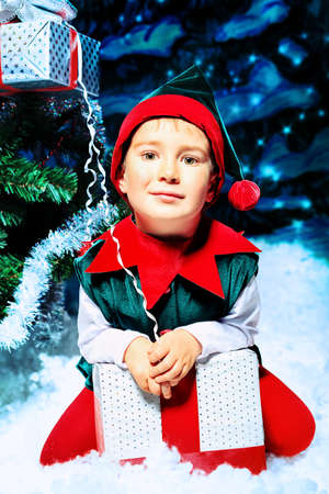 Little boy in Christmas elf costume posing over christmas background. photo