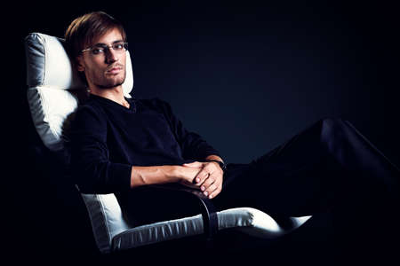 Portrait of a handsome man sitting in the armchair over black background. Stock Photo - 15771212