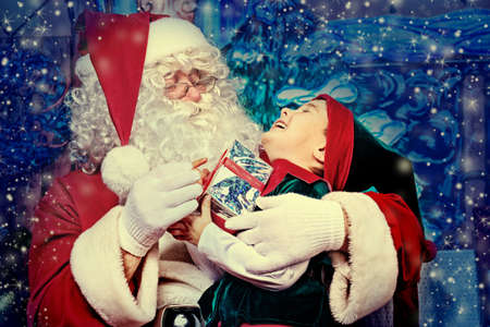 Santa Claus sitting with a little cute boy elf over Christmas background.  photo