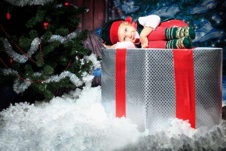 duendes de navidad: Ni�a en traje de Duende de la Navidad posando sobre fondo de Navidad.