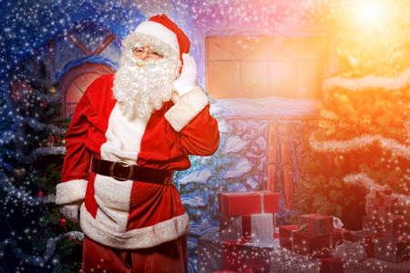 Père Noël avec des cadeaux posant sur fond de Noël.