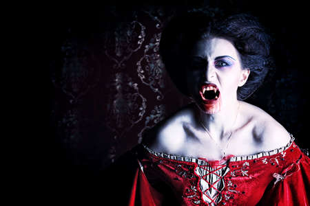 vampire: Close-up portrait of a bloodthirsty female vampire. Stock Photo