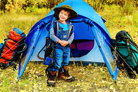 boot camp: Cute little boy with backpack and tent outdoor.