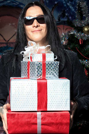 Portrait of a grunge young man with presents. Christmas. photo
