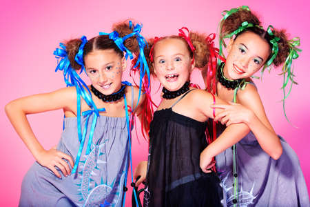 Portrait of three beautiful girls with festive make-up, hairstyle and dress.  photo
