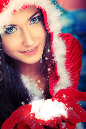 santa: Beautiful young woman in Santa Claus clothes over Christmas background.