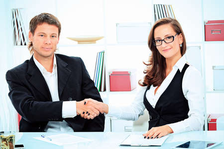international business agreement: Business woman and businessman shaking hands at the meeting in the office.
