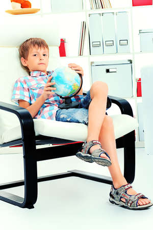 Cute boy sitting in armchair with his globe at home.