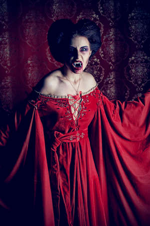 godforsaken: Portrait of a bloodthirsty female vampire over red vintage background.