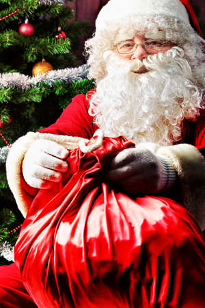 saint nick: Santa Claus sitting with presents over Christmas background.