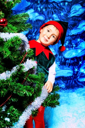 christmas costume: Little boy in Christmas elf costume posing over christmas background.