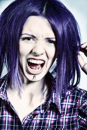 Portrait of a shouting punk girl with purple hair.  photo