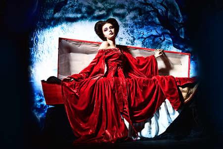 Krwiożerczy wampir kobieta wstaje z trumny na cmentarzu w nocy.