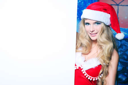 snow maiden: Sexy young woman in Christmas clothes holding white board over Christmas background.
