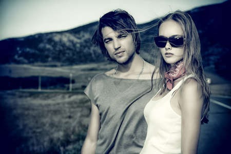 fashion boy: Couple of modern young people posing on a road over picturesque landscape.