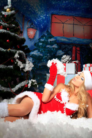 Beautiful young woman in Santa Claus clothes over Christmas background. Stock Photo - 15882883