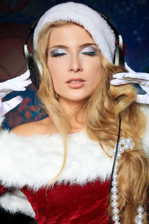 Beautiful young woman in Santa Claus clothes and headphones over Christmas background. Stock Photo - 15886974