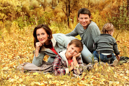Happy family having a rest outdoor in the autumn park. photo