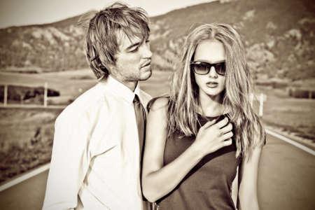 jovenes enamorados: Pareja apasionada de los jóvenes posando en un camino a través de un pintoresco paisaje.