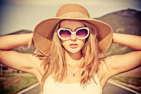 gafas de sol: Joven y bella mujer posando en un camino sobre el paisaje pintoresco.