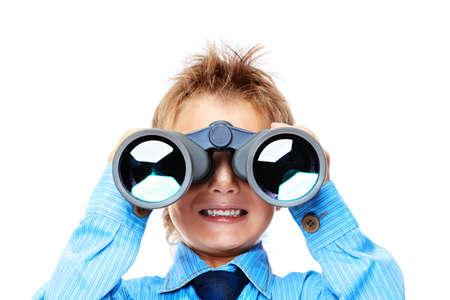 schoolkid search: Ni�o peque�o curioso est� mirando a trav�s de binoculares. Aislado sobre fondo blanco. Foto de archivo