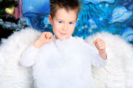 Beautiful little angel boy over Christmas background. photo