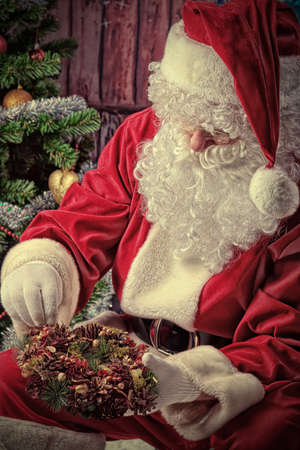 pine wreath: Santa Claus posing with presents over Christmas background.
