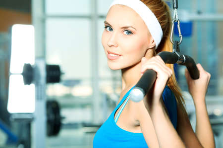 sportive: Young sporty woman doing exercises in the gym centre. Stock Photo