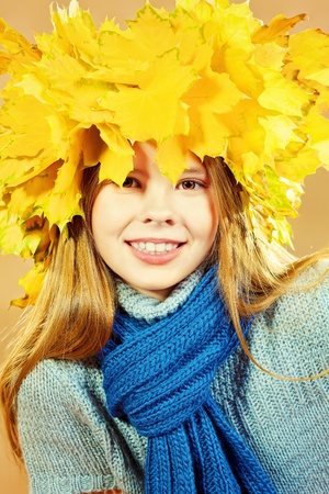 Portrait of a smiling girl in autumn clothes and a hat of maple leaves. Stock Photo - 15887003