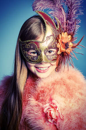 Beautiful little girl in festive dress and mask posing at studio. photo
