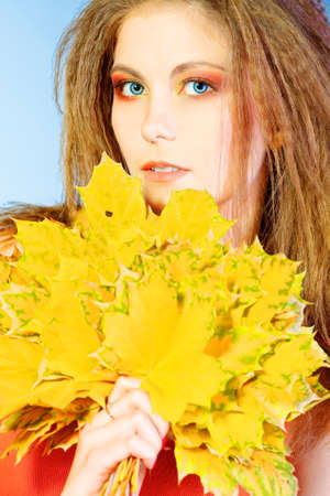 Beautiful girl holding bouquet of autumn leaves. photo