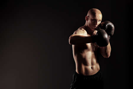 boxer: Portrait of an aggressive boxer in gloves posing at studio.