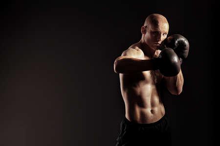 boxeadora: Retrato de un boxeador agresivo en los guantes posando en el estudio.