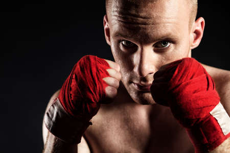 active lifestyle: Portrait of a muscular boxer in red gloves posing at studio.