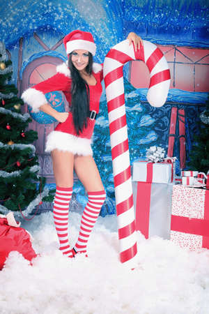 erotic fantasy: Beautiful young woman in Santa Claus clothes over Christmas background.