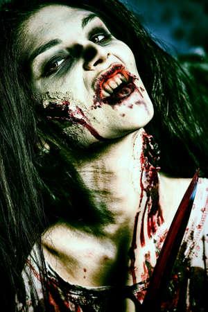 satanas: Zombi sanguinario con un cuchillo de pie en el cementerio de la noche en la niebla y la luz de la luna.